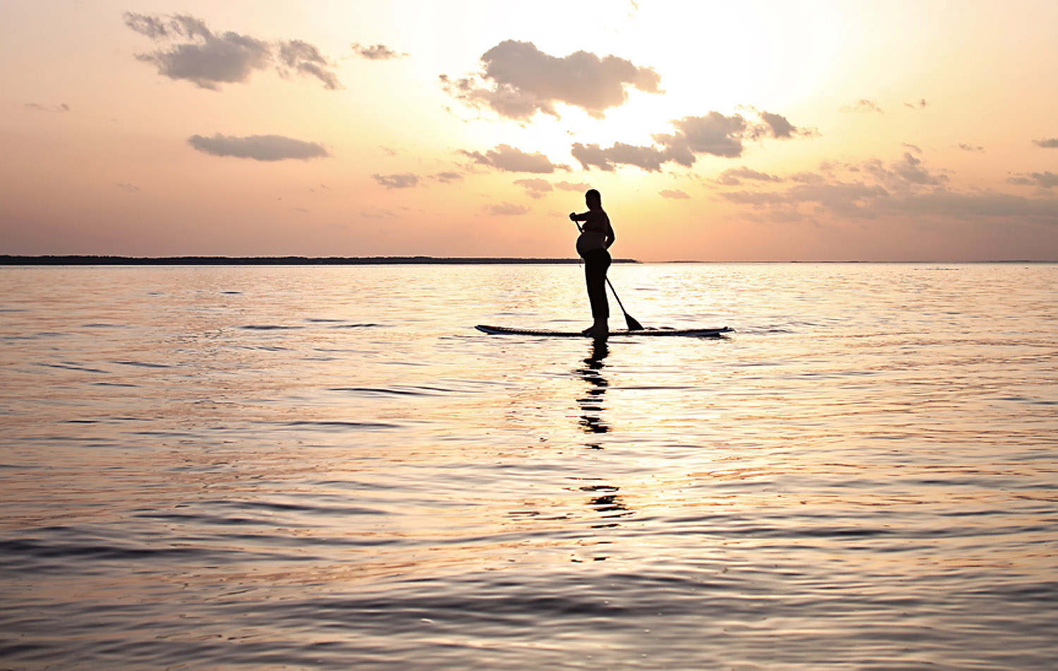 Pregnant woman stand up paddle boarding at sunset in OBX NC